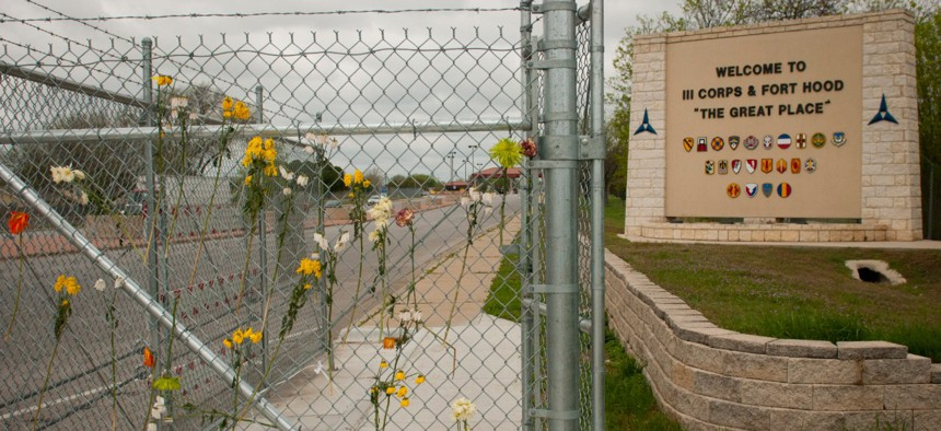 Flowers placed by anonymous supporters hang in a fence at Fort Hood's Rancier gate in 2014.