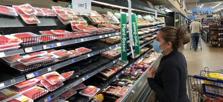 A shopper looks beef at a Kroger store in Atlanta underneath a sign limiting shoppers to three packages of ground beef on Tuesday, May 5, 2020.