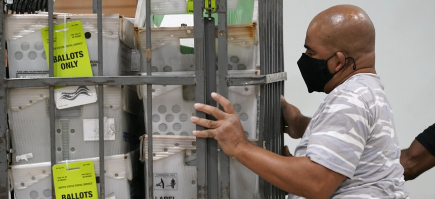 An employee loads vote-by-mail ballots into a truck for transport to a local U.S. Postal Service office at the Broward Supervisor of Elections Office on Sept. 24 in Lauderhill, Fla.