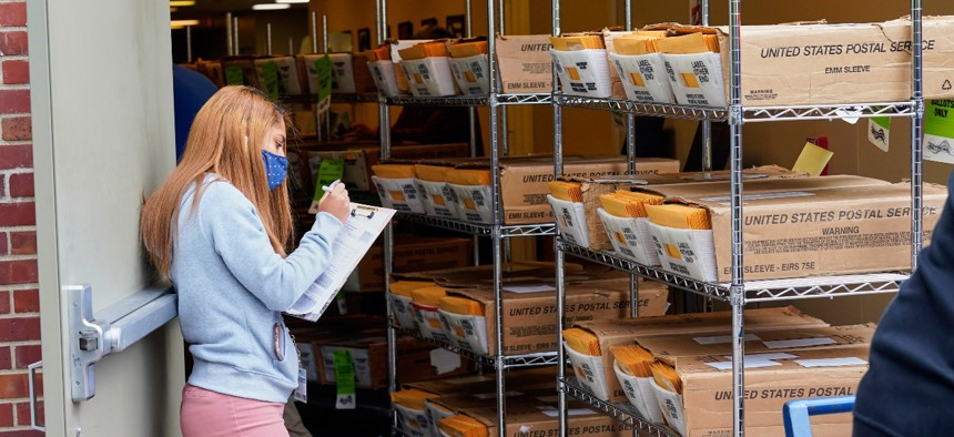 A worker logs boxes containing mail-in ballots, part of the first batch of 111,000 mail-in ballots, as they are shipped from the Douglas County Election Commission's office to the post office, in Omaha, Neb., on Sept. 28.