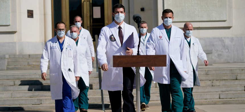 Dr. Sean Conley, physician to President Trump, center, and other doctors walk out to talk with reporters at Walter Reed National Military Medical Center on Monday.