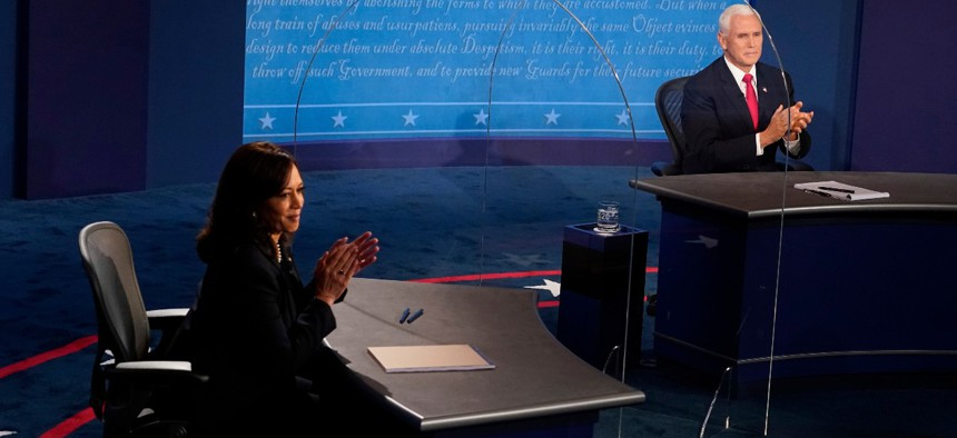Sen. Kamala Harris, D-Calif., and Vice President Mike Pence applaud after the vice presidential debate Wednesday