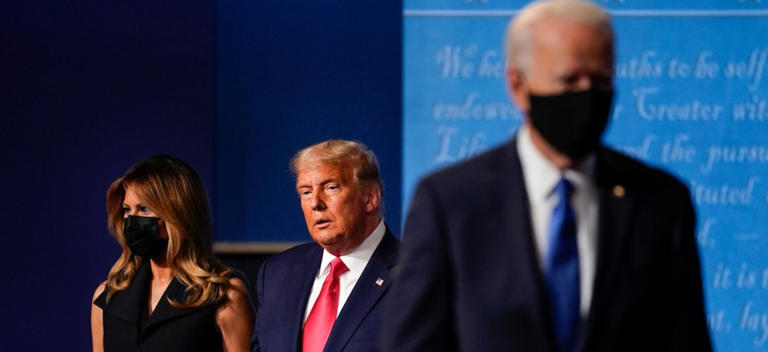 First Lady Melania Trump, left, and President Trump, center, remain on stage as Democratic presidential candidate former Vice President Joe Biden, right, walks away at the conclusion of the second and final presidential debate on Oct. 22.