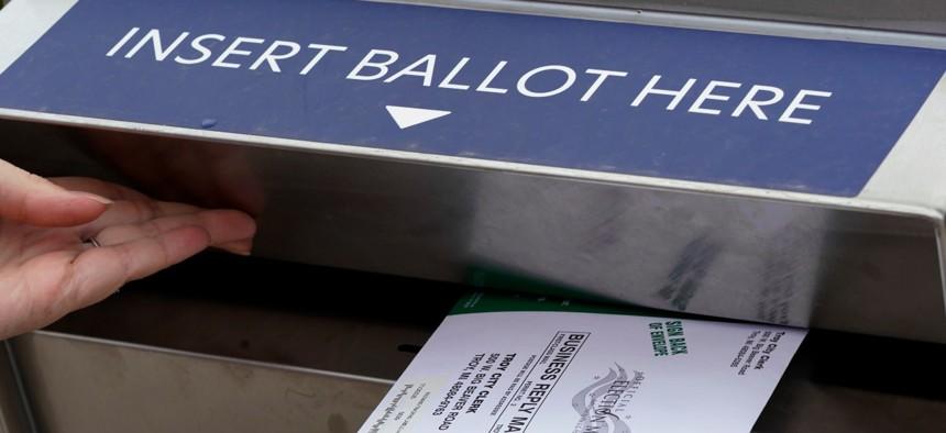 Nikki Schueller inserts her absentee voter ballot into a drop box, Thursday, Oct. 15, 2020, in Troy, Mich.