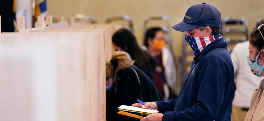 Bruce Lowell looks down at his ballot as he enters a voting booth at an early voting location.