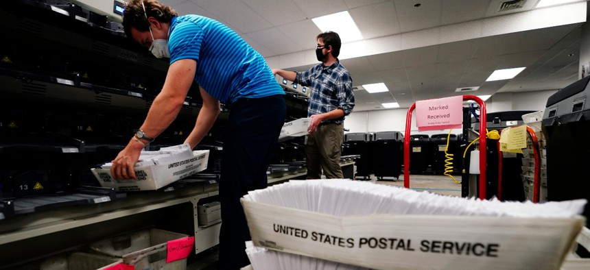 Kyle Hallman, left, and Michael Imms, with Chester County Voter Services, gather mail-in ballots being sorted for the general election in West Chester, Pa.