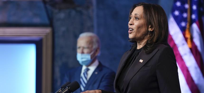 President-elect Joe Biden listens as Vice President-elect Kamala Harris speaks Tuesday in Delaware.