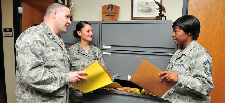 Lt. Col. Gregory Goforth discusses accounting files with members of the 145 Comptroller Flight.