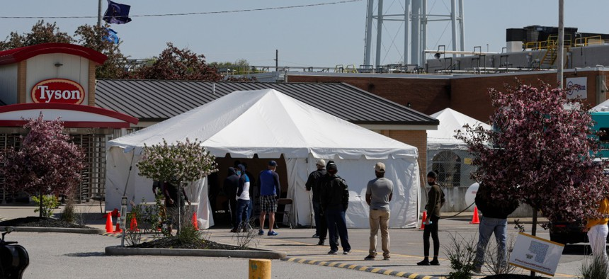 Workers wait in line to enter the Tyson Foods pork processing plant in Logansport, Ind., on May 7.