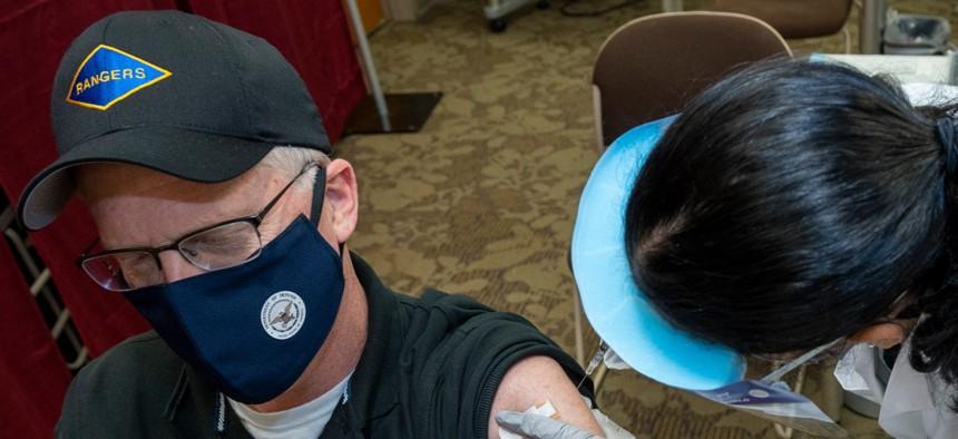 Acting Defense Secretary Chris Miller receives a COVID-19 vaccine from Navy Hospitalman Samantha Alvarez at Walter Reed National Military Medical Center on Dec. 14.