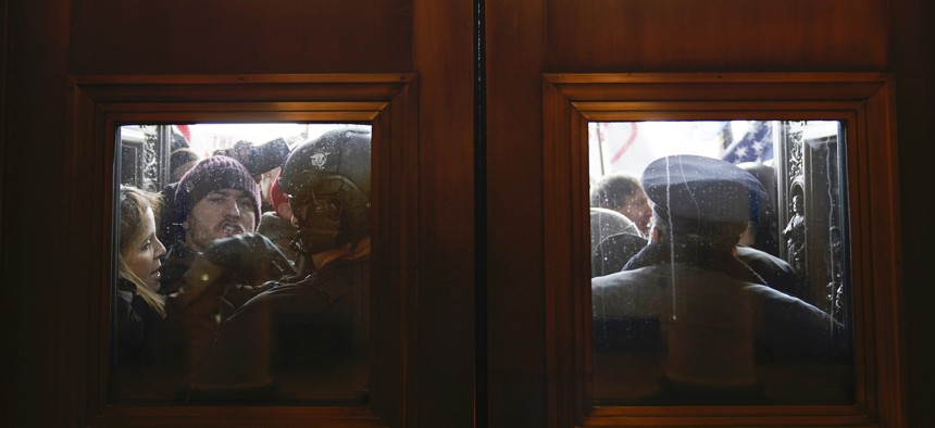 U.S. Capitol Police try to hold back protesters outside the east doors to the House side of the U.S. Capitol on Wednesday.