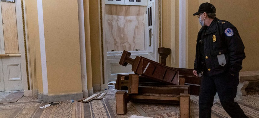 A U.S. Capitol Police officer walks past damage in the early morning hours of Jan. 7, after protesters stormed the Capitol on Wednesday.