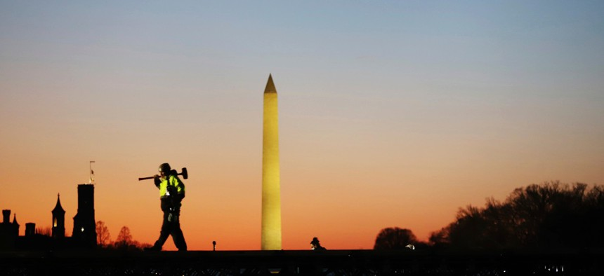 A construction worker carries a hammer on his shoulder on Wednesday at the National Mall in Washington, as a stage is prepared for Joe Biden's presidential inauguration.