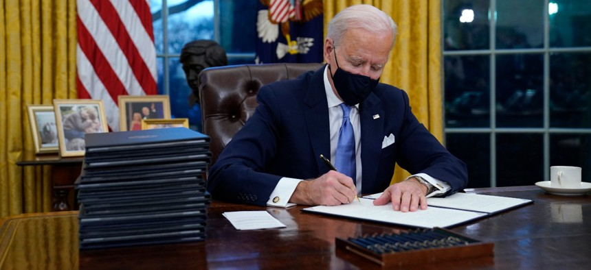 President Biden signs his first executive order in the Oval Office of the White House on Wednesday.