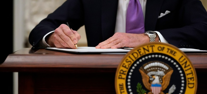 President Biden has signed a flurry of executive orders since taking office. Above, he signs executive orders after speaking about the coronavirus in the State Dinning Room of the White House, Thursday, Jan. 21, 2021, in Washington.