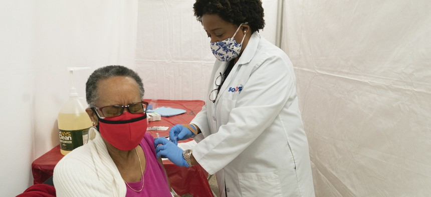 Dr. Jacqueline Delmont, Chief Medical Officer at Somos, gives Helen Washington, 76, the first dose of the coronavirus vaccine at a pop-up COVID-19 vaccination site at St. Luke's Episcopal Church in New York.