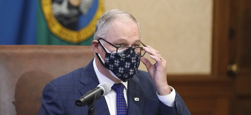 Governor Jay Inslee wears a double mask as he speaks before signing the first bill to be signed into law during the 2021 legislative session, Monday, Feb. 8, in Olympia.