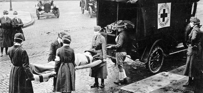 With masks over their faces, members of the American Red Cross remove a victim of the Spanish Flu from a house at Etzel and Page Avenues, St. Louis, Missouri in 1918.