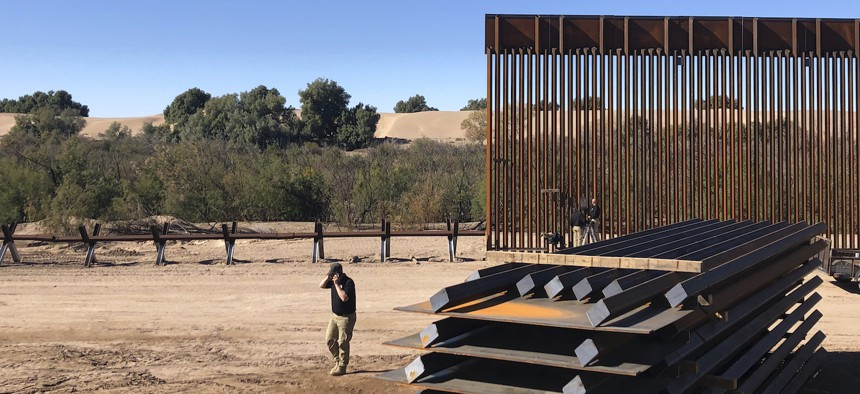 A man passes new border wall sections, right, as they replace the old fencing, left, near Yuma, Arizona in January, 2020.