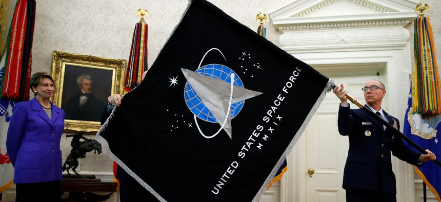 Secretary of the Air Force Barbara Barrett, left, watches Chief Master Sgt. Roger Towberman holds the United States Space Force flag as it is presented in the Oval Office of the White House, Friday, May 15, 2020.