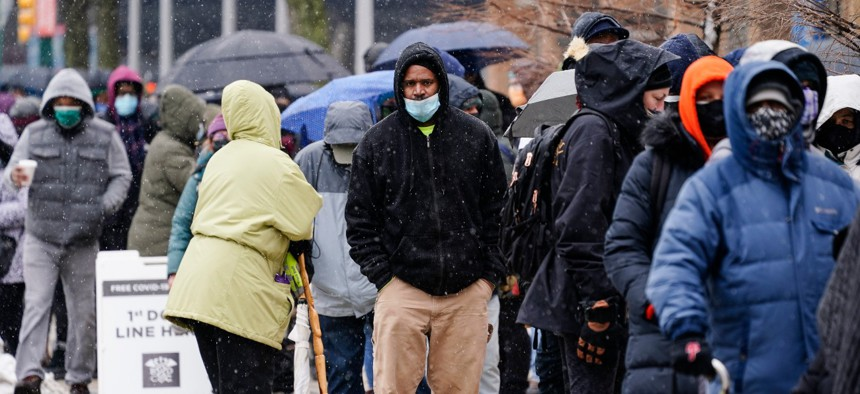 People wait in line at a 24-hour, walk-up COVID-19 vaccination clinic hosted by the Black Doctors COVID-19 Consortium at Temple University's Liacouras Center in Philadelphia on Feb. 19, 2021.