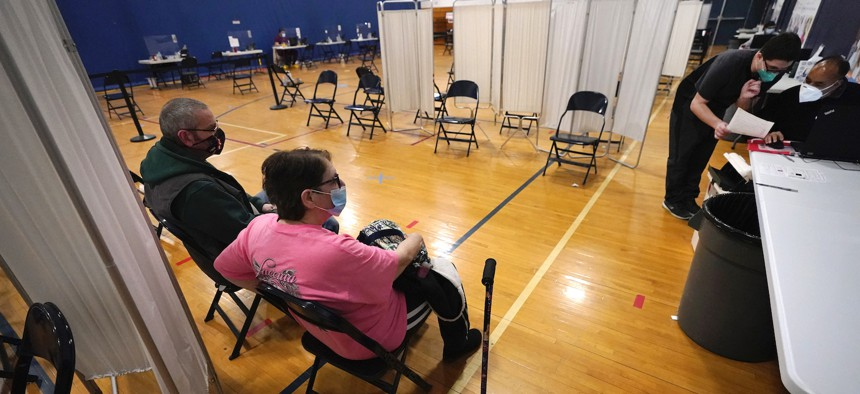 Roberta Zangri-Briggs, of Methuen, Mass. waits with her husband Allen Briggs in the observation area, after she received Moderna's COVID-19 vaccine at Lawrence General Hospital's vaccination site on Feb. 25 in Massachusetts.
