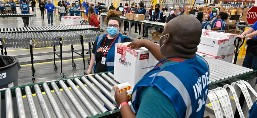The first box containing the Johnson & Johnson COVID-19 vaccine heads down the conveyor to an awaiting transport truck at the McKesson facility in Shepherdsville, Ky., on Monday.