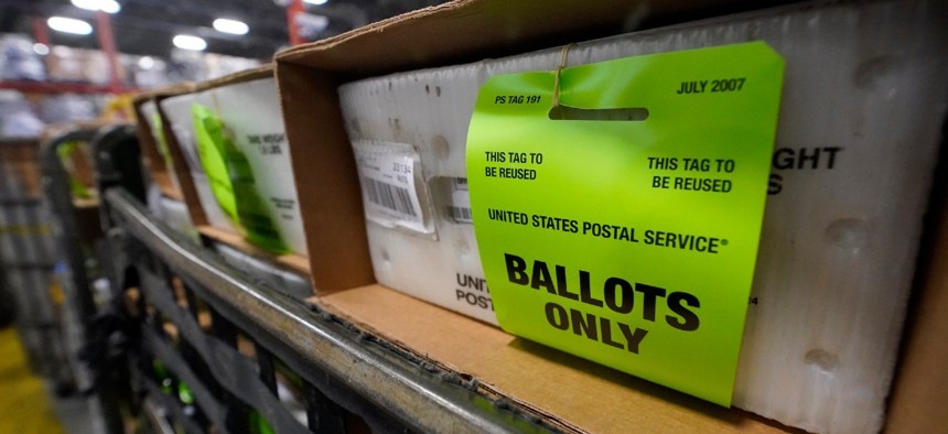 A cart holding vote-by-mail ballots is seen before being loaded into a truck for transport to a local U.S. Postal Service office on Oct. 1, 2020, at the Miami-Dade County Elections Department in Doral, Fla.