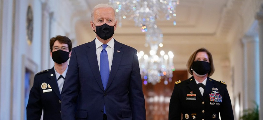 President Biden walks with U.S. Air Force Gen. Jacqueline Van Ovost, left, and U.S. Army Lt. Gen. Laura Richardson before speaking at an event to mark International Women's Day on March 8.