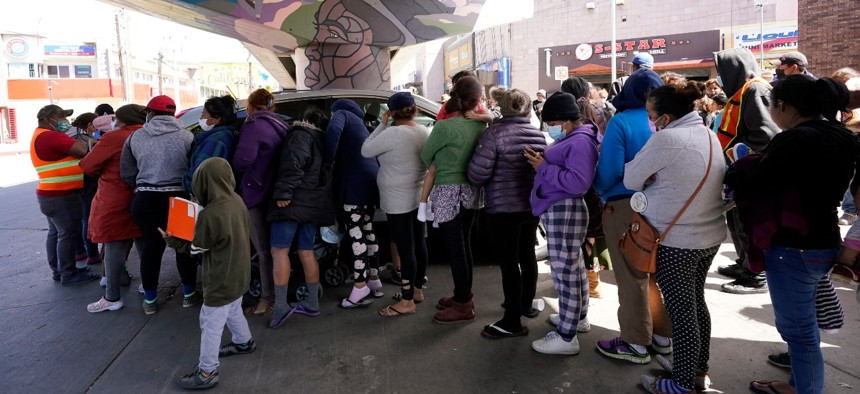 People surround a car as it arrives carrying food donations at a makeshift camp for migrants seeking asylum in the United States at the border crossing on March 12, 2021, in Tijuana, Mexico.
