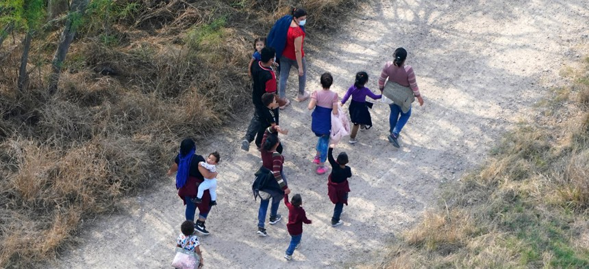 Migrants walk on a dirt road after crossing the U.S.-Mexico border on March 23 in Mission, Texas.