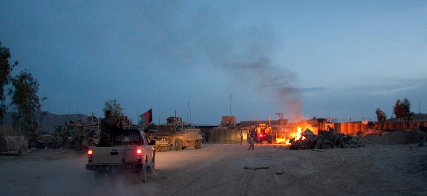 An Afghan National Army pickup truck passes parked U.S. armored military vehicles, as smoke rises from a fire in a trash burn pit at Forward Operating Base Caferetta Nawzad, Helmand province south of Kabu in 2011.