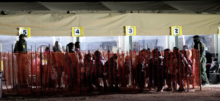 Migrants are seen in custody at a U.S. Customs and Border Protection processing area under the Anzalduas International Bridge, in Mission, Texas on March 19.