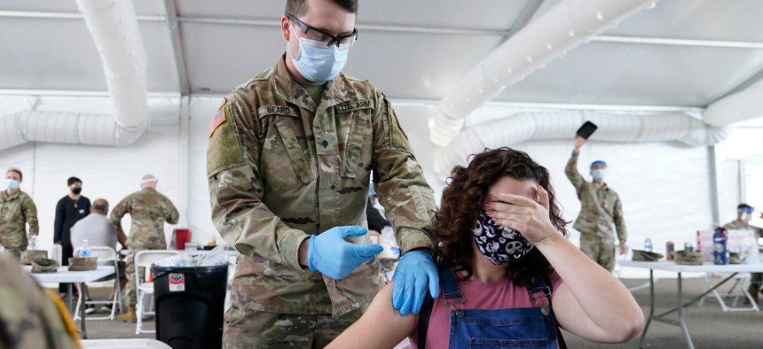 Leanne Montenegro, 21, covers her eyes as she doesn't like the sight of needles, while she receives the Pfizer COVID-19 vaccine at a FEMA vaccination center at Miami Dade College in Miami.