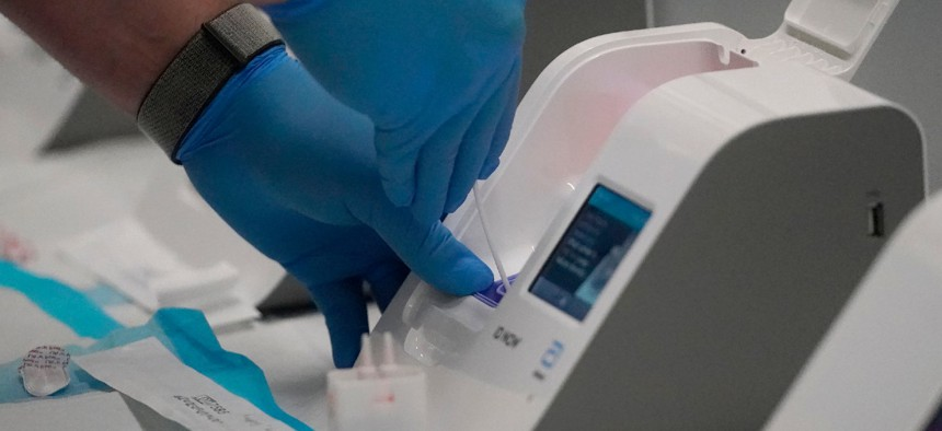 A Dignity GoHealth worker uses an Abbott ID Now rapid antigen testing machine for United Airlines passengers who took tests at a COVID-19 rapid testing site at San Francisco International Airport in October.