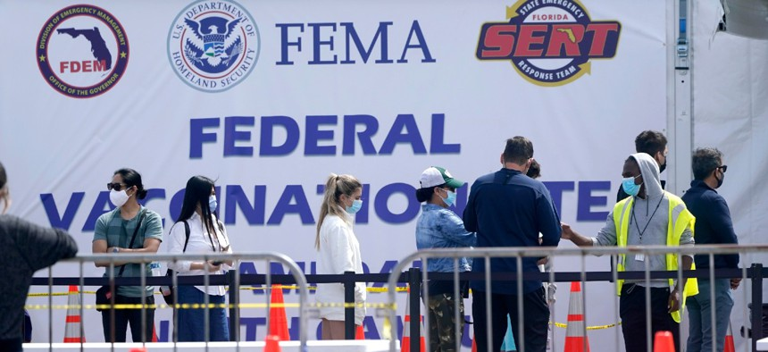 People wait in line to receive a COVID-19 vaccine at a FEMA vaccination center at Miami Dade College on April 5. With FEMA leading the federal vaccination effort in addition to the agency's more traditional disaster-response duties, employee burnout is a concern.