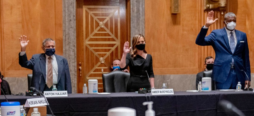 From left, nominees for Postal Service Governors Anton Hajjar, Amber McReynolds and Ronald Stroman, are sworn in at a Senate Homeland Security and Governmental Affairs Committee hearing on Thursday.
