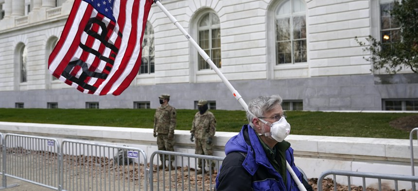 A protester walks past the Russell Senate Office Building on Capitol Hill in Washington on Friday, Jan. 8, 2021.