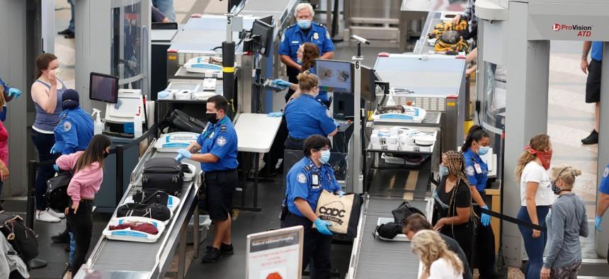 Transportation Security Administration agents process passengers at Denver International Airport in Denver in June 2020.