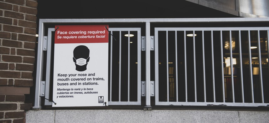 A sign outside the metro station at Mt Vernon Square 7th St-Convention Center informs riders that face coverings are required in the station and on trains.