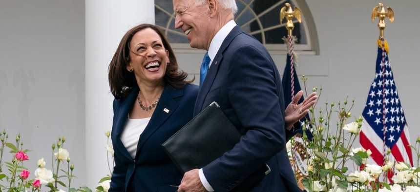 Vice President Kamala Harris and President Biden smile and walk off after speaking about updated guidance on mask mandates, in the Rose Garden of the White House on May 13.