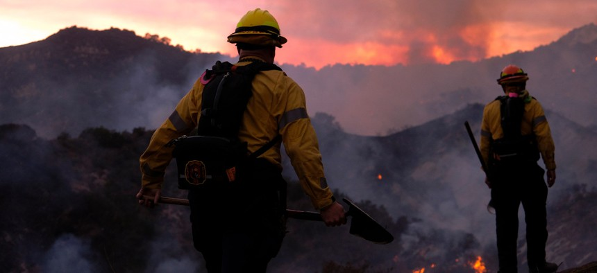 Firefighters watch as smoke rises from a brush fire scorching at least 100 acres in the Pacific Palisades area of Los Angeles this week. The Forest Service is struggling to recruit and retain wildland firefighters in California.