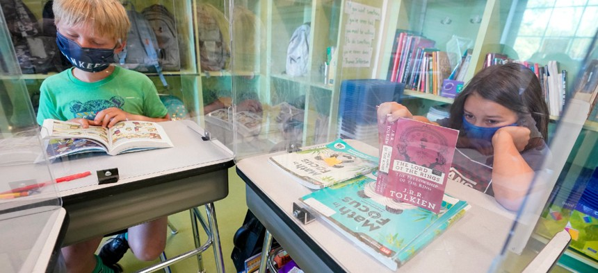 Fifth graders wear their face masks and are separated by plexiglass as they do their class work at the Milton Elementary School in Rye, N.Y., on May 18.