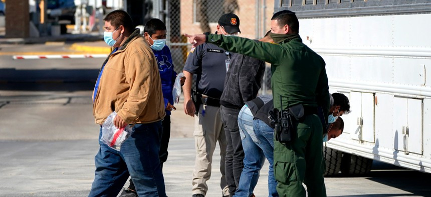 A U.S. Customs and Border Protection officer, right, instructs a migrant to walk toward the McAllen-Hidalgo International Bridge while deporting a group of migrants to Mexico in March.