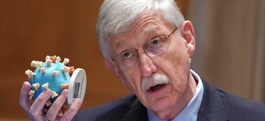 Dr. Francis Collins holds up a model of the coronavirus as he testifies before a Senate Appropriations Subcommittee on May 26.