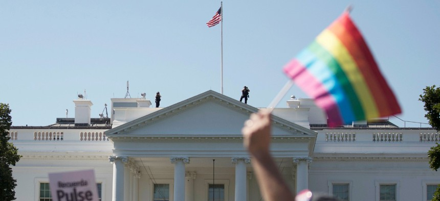 Equality March for Unity and Pride participants march past the White House in Washington in 2017. Under the Biden administration agencies are recognizing LGBTQ+ employees.
