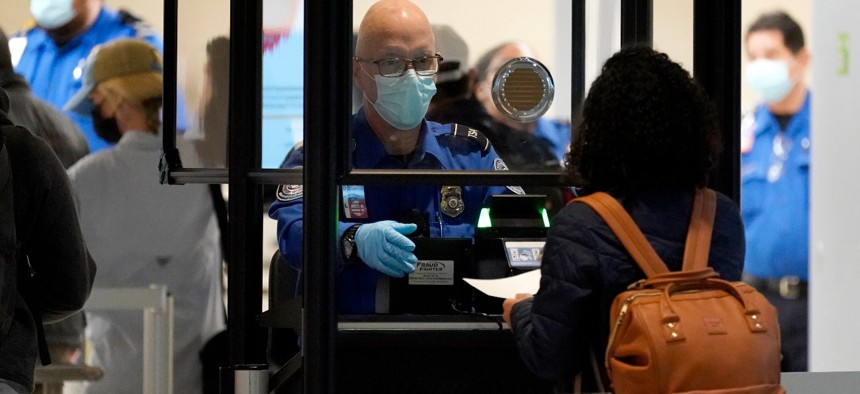 A TSA agent assist a traveler at a security checkpoint at Love Field Airport in Dallas. There were fewer air travelers in the United States last year, but a higher percentage of them were carrying guns.