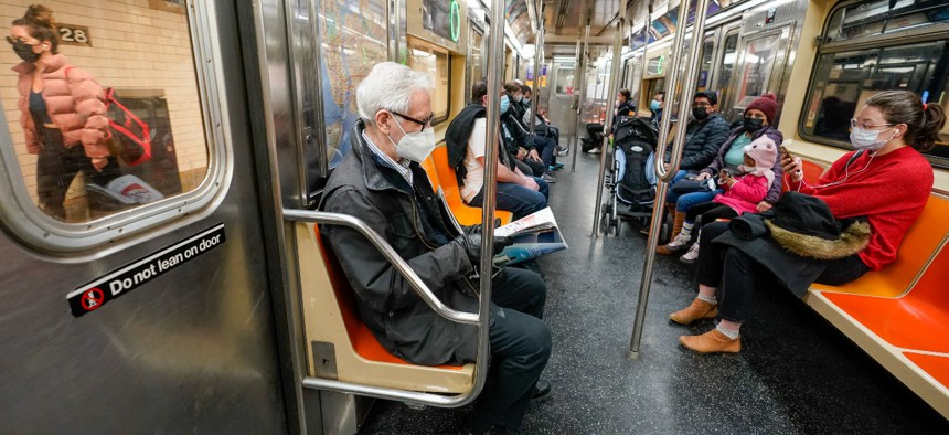 Commuters wear face masks on the M Train in New York in March.