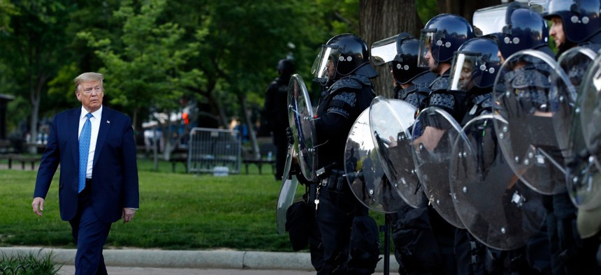 President Trump walks past police in Lafayette Park after he visited outside St. John's Church across from the White House Monday, June 1, 2020, in Washington.