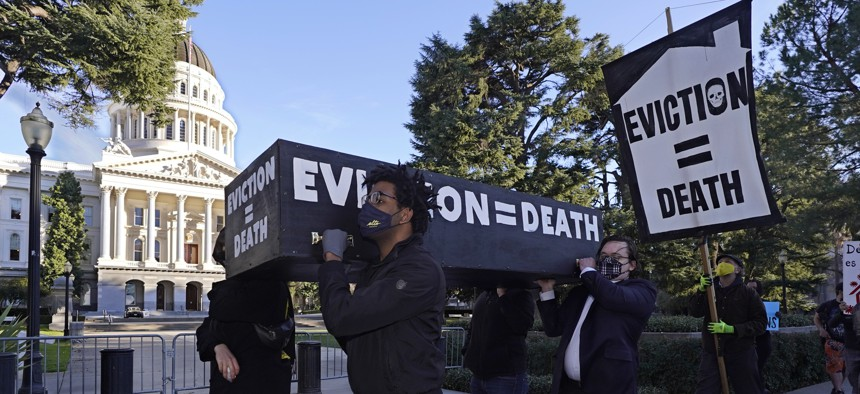 Demonstrators calling for lawmakers and Gov. Gavin Newsom to pass rent forgiveness and stronger eviction protections legislation, carry a mock casket past the Capitol in Sacramento, Calif., on Monday, Jan. 25, 2021.